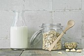 Muesli ingredients: oat in a storage jar, a bottle of milk and cashew nuts