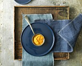 Ground turmeric on a ladle on a plate on a wooden tray