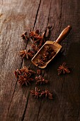 Star anise on a rustic wooden table with a small wooden scoop