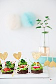 Pumpernickel rounds with vegan pea and mint cream decorated with heart sticks
