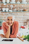 Ältere Dame stützt sich lächelnd auf Küchentisch vor e-Book