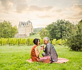 A couple drinking wine at a picnic on a meadow with a vineyard and a castle in the background