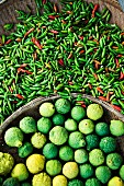 Fresh chilli peppers and kaffir limes at a market (Thailand, Asia)