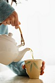 A woman pouring tea from an oriental teapot into a tea mug