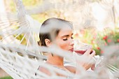 A woman in a hammock drinking a cocktail