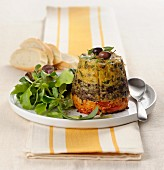 A three-layer vegetable cake with herbs, olives and tomatoes
