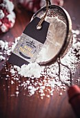 A sieve with icing sugar and a Christmas gift tag