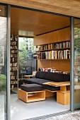 Blick auf maßgefertigtes Bücherregal und Polstersofa mit Ablagefläche