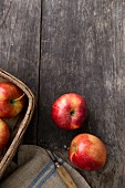 Red apples on a wooden board with a peeler and a basket