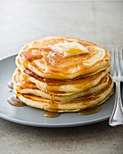 A stack of buttermilk pancakes on a plate with butter and maple syrup
