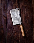 An antique meat cleaver on a wooded board