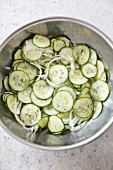 Cucumber salad (sliced cucumber and onions) in a stainless steel bowl