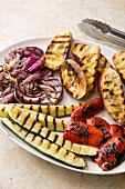 Ingredients for grilled panzanella (bread salad): grilled courgettes, red onions, peppers and grilled bread