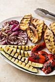 Zutaten für gegrillten Panzanella-Brotsalat: gegrillte Zucchini, rote Zwiebeln, Paprika und Grillbrot