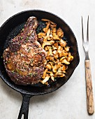 Ribeye steak in a cast-iron pan with sautéed mushrooms