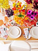 Colorful table decoration with flowers and white dishes