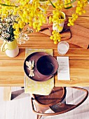 Place setting with wooden cutlery and yellow place mat, bouquet of wax herbs and yellow flower branch