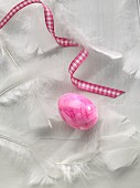 A coloured egg with a ribbon and feathers