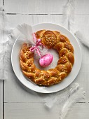 An Easter wreath with a pink Easter egg and a white feather