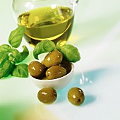 Green olives with olive oil and basil on a white surface