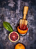 Blood oranges and a wooden citrus press on a metal surface