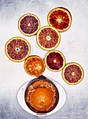 Blood orange halves with a stainless steel citrus juicer on a light metal surface