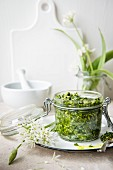 A jar of wild garlic pesto and fresh wild garlic with flowers
