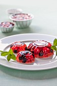 Jelly with red fruit on a white plate garnished with mint