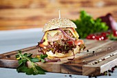 A mini hamburger with oak leaf lettuce, tomatoes, onions and cheese
