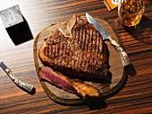 Angeschnittenes gegrilltes T-Bone-Steak auf Holzteller mit Steakmesser
