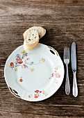 An old white porcelain plate decorated with flowers with silver cutlery and two slices of baguette on the wooden table