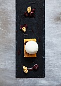 A ball of honey and rosemary parfait on a slice of carrot cake, halved cherries, cherry sauce and crispy muesli on a slate platter