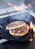 Fladenbrot-Sandwich mit Schwarzkümmel, Thunfisch, Tomaten, Kapern und Frühlingszwiebeln in Grillpfanne