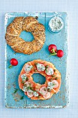 A bagel topped with smoked salmon, capers, radishes and dill sauce