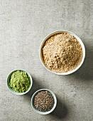 Maca-Pulver, Gerstengraspulver und Chiasamen in verschiedenen Schalen (Draufsicht)
