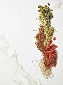 Kürbiskerne, Leinsamen, Gojibeeren, Hanfsamen, weisse und rote Quinoasamen (Draufsicht)