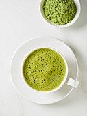 A cup of matcha tea and a bowl of tea powder (see above)