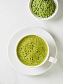 Eine Tasse Matchatee und Teepulver im Schälchen (Draufsicht)
