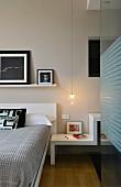 Schlafzimmer mit modernem Nachttischelement unter Pendelleuchte