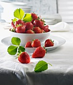 Fresh strawberries and leaves in a porcelain bowl