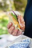 A person holding a picnic sandwich with salami and salad