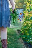 Woman standing in garden holding flowers