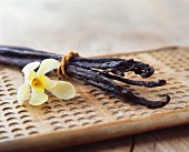 Vanilla pods and a yellow flower on a wooden board