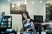 A young waitress wearing a hat working in a cafe