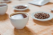 A cup of coffee and coffee beans at a tasting session