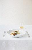 A fish dish with mushrooms on a white plate on a table laid with a white cloth