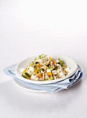 Warm orzo salad with vegetables, herbs and cream cheese