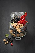 Redcurrants, blackcurrants and white currants in a jar