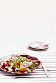 Vegetable salad with beef, pine nuts and feta cheese