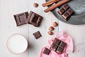 Stillleben mit Schokoladenstücken, Zimt, Nüssen und Milchglas (Aufsicht)